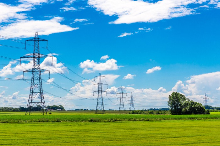 A row of transmission pylons stretching into the horizon against blue skies.