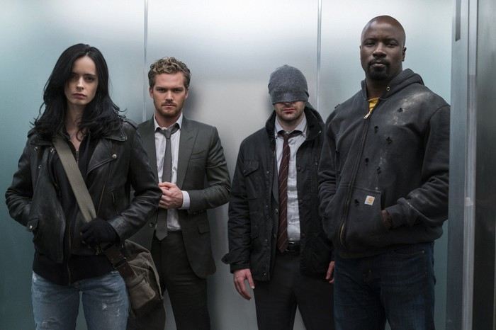 Jessica Jones, Danny Rand, Matt Murdock, and Luke Cage standing in a stainless steel elevator.