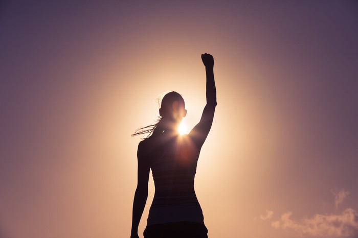 Woman raising her fist in silhouette against a golden sunrise.