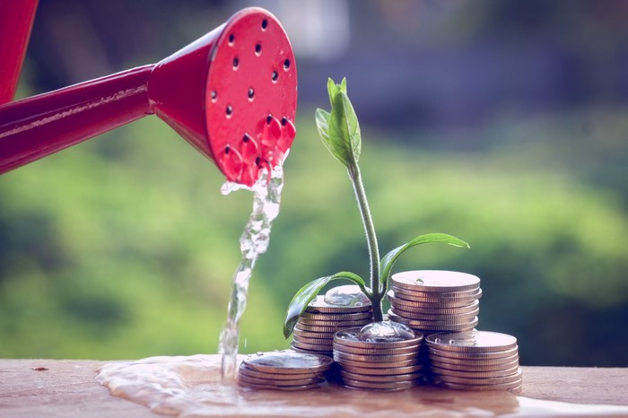 A pile of coins with a plant growing out of the center, and watering can pouring onto it.
