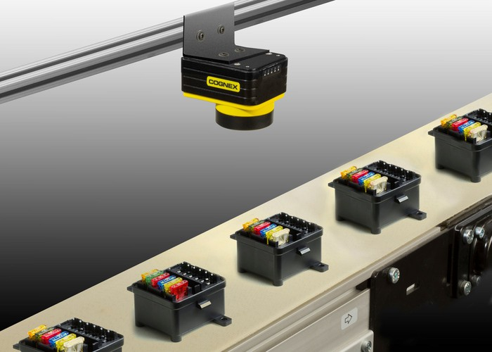 A Cognex machine vision system mounted above conveyor belt with various objects.