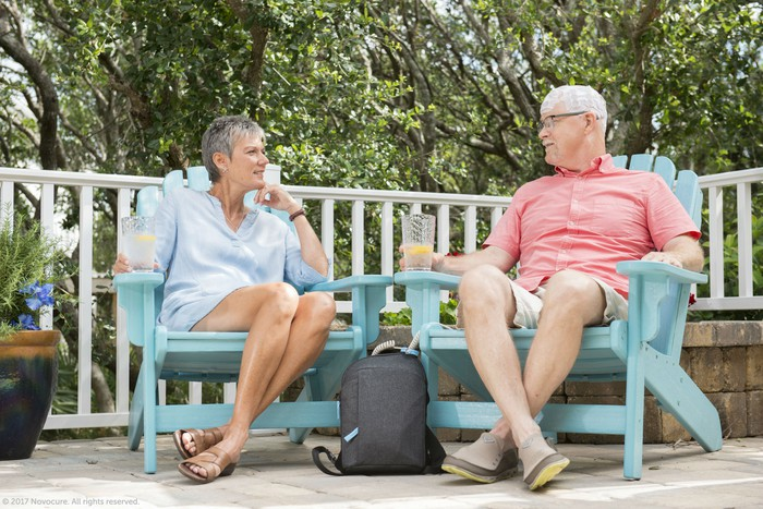 A couple sitting together on a deck with the man using an Optune device.