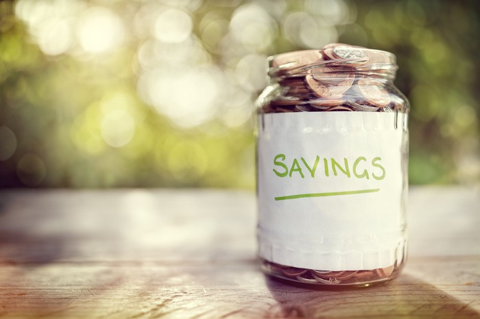 """A glass jar on a table outdoors is filled to the brim with coins and is labeled with the word """"savings."""""""