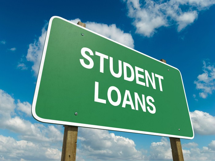 """""""Student Loans"""" printed on a green highway sign, with a cloudy sky in the background."""