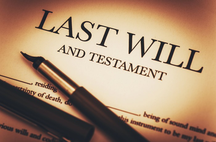 """A paper that reads """"Last will and testament,"""" with a pen lying on top of it."""