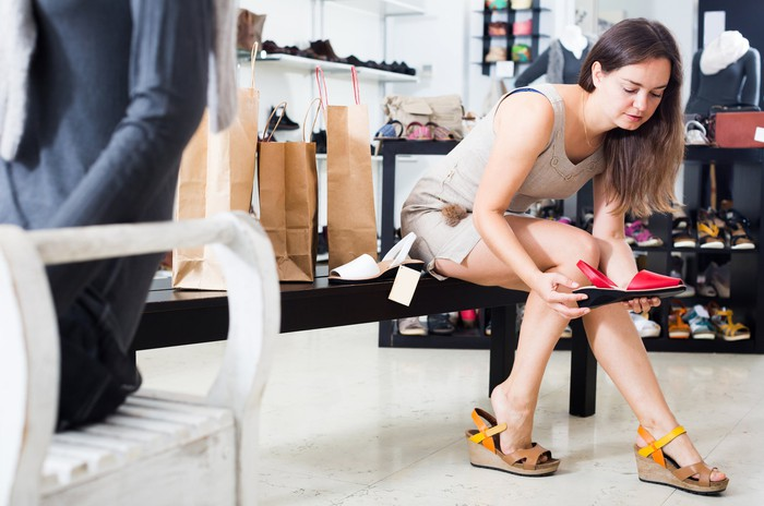 A woman holds a shoe in a shoe store