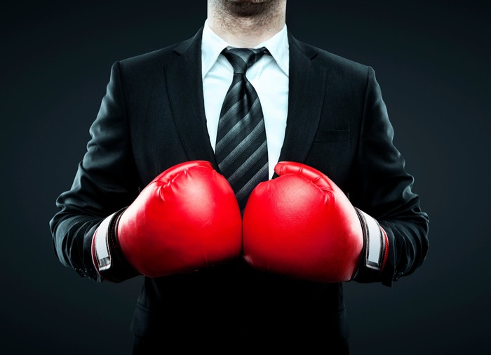 A businessman wearing a suit and a pair of bright red boxing gloves.