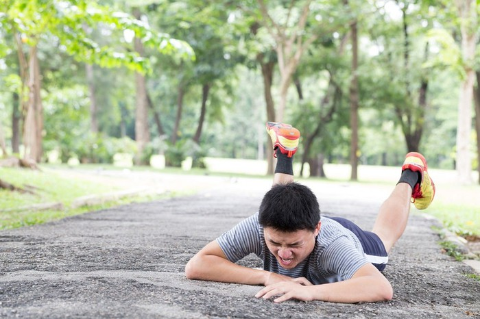 A fallen runner grimaces while lying on the ground