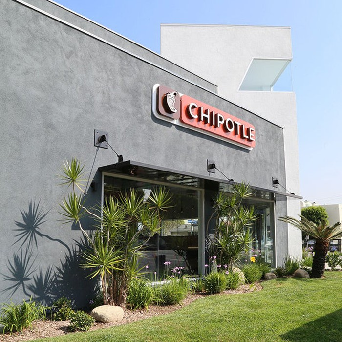 The exterior of a Chipotle location, with desert plants surrounding two picture windows