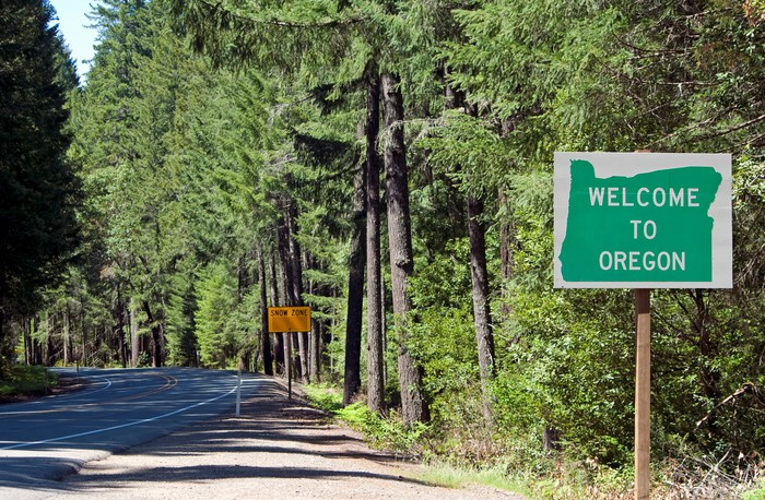 "a road cutting through a forest, with a sign that says ""welcome to Oregon"""