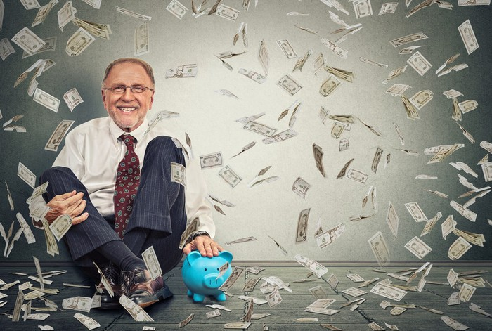 Smiling man sitting on floor with a piggy bank as dollar bills fall from the sky on him.