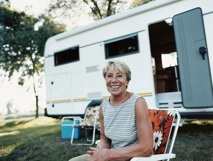 A senior woman smiling while sitting in front of a camper
