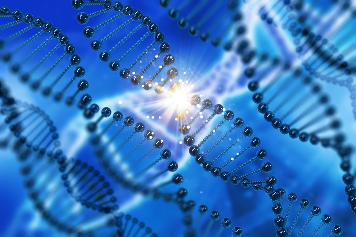 DNA strands on blue background with spark of light at center of one DNA strand