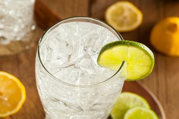 A glass of sparkling water, garnished with a lime.