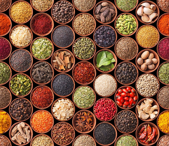 Overhead view of various bowls full of spices, herbs, and other food ingredients