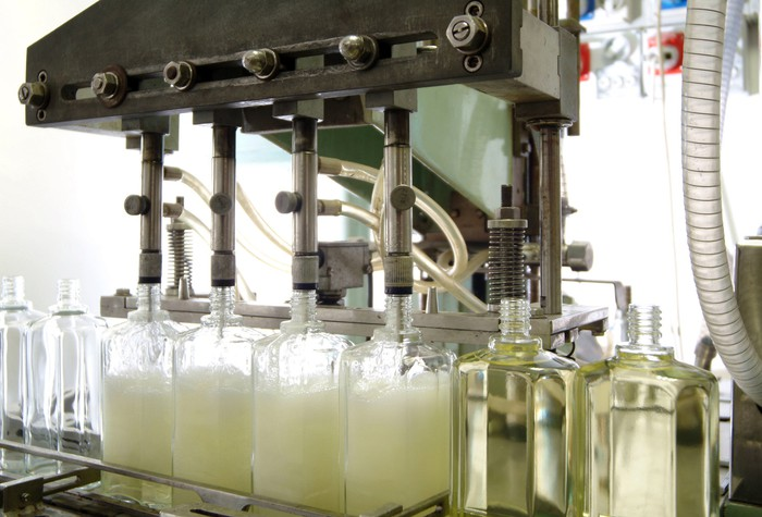 A machine at a cosmetics factory filling empty plastic bottles with liquid.
