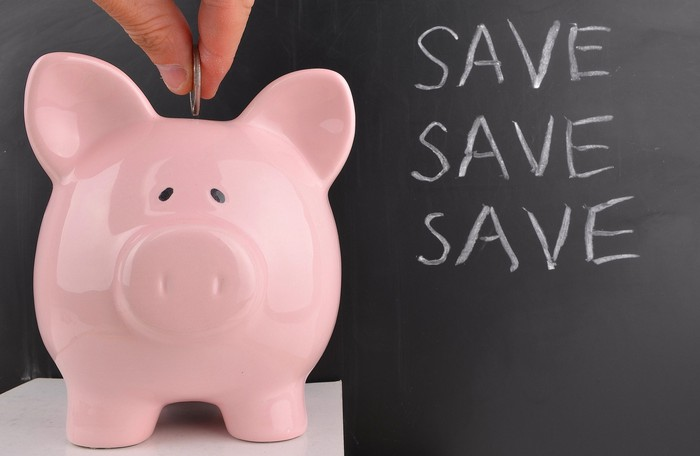 """Piggy bank with the words """"save save save"""" alongside it"""