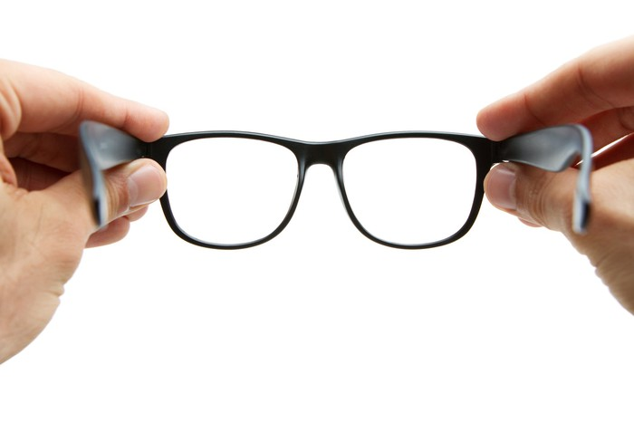 Hands hold out a pair of eyeglasses at arm's length, as it looking through them.