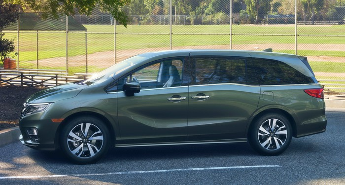 A green 2018 Honda Odyssey minivan is parked next to a baseball field.