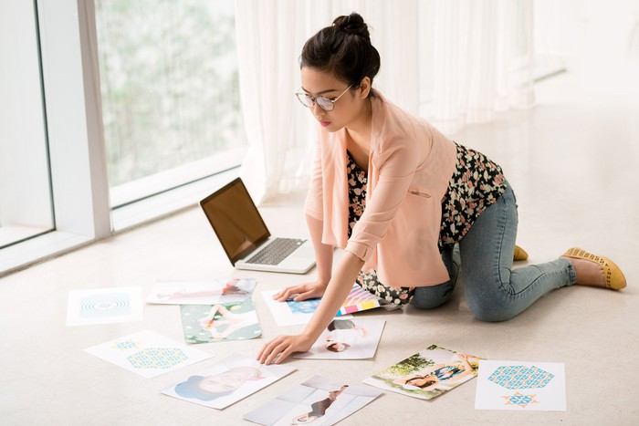 Person on floor with paper images spread out next to a computer.