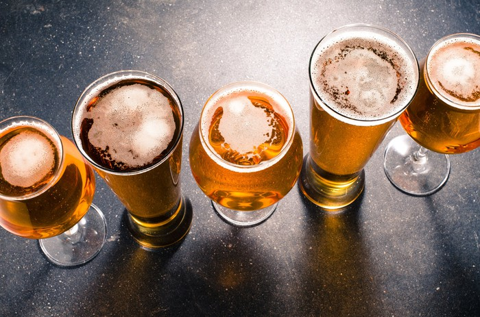 Five different beer glasses lined up filled with different beer.