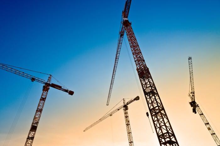 Four cranes against a skyline