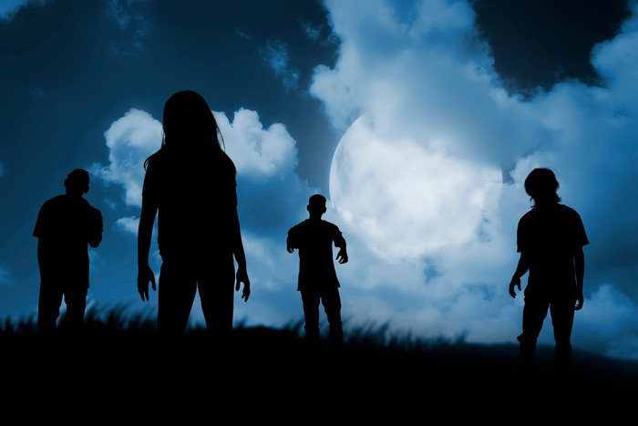 Zombies walking on a hill in the moonlight.