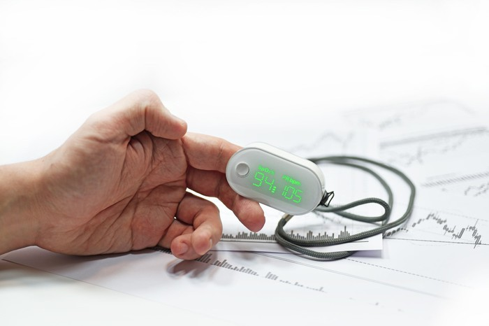 Hand resting on top of papers with index finger in pulse oximeter
