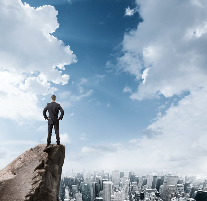 A businessman looking out at a city from a perch above the clouds
