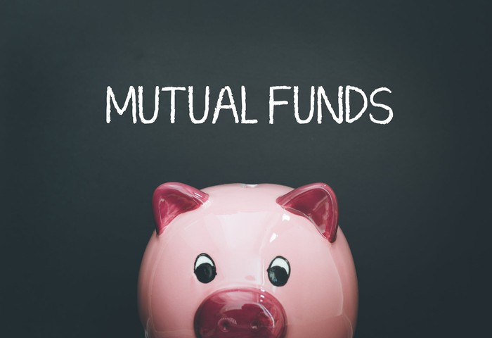 "pink piggy bank in front of blackboard on which is written ""mutual funds"""