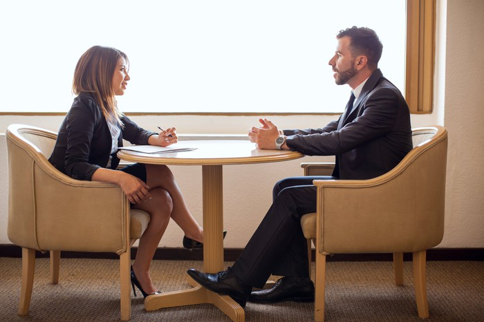 Male and female professional having a discussion