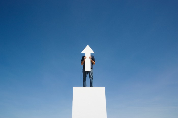 A man standing on a white square pillar against a blue sky and holding a white arrow the size of his body that is facing up.