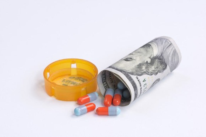 Capsules, colored red and blue, spill out of a hundred-dollar bill wrapped up to look like a tipped-over prescription bottle.