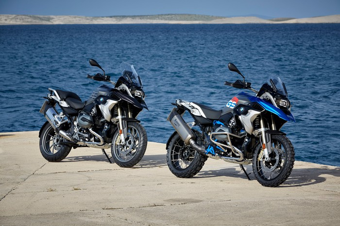 Two BMW R 1200 GS motorcycles, in black with blue trim, parked on a sunny waterfront.