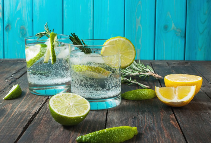 Two glasses containing seltzer water with lemon and lime wedges on a wooden table.
