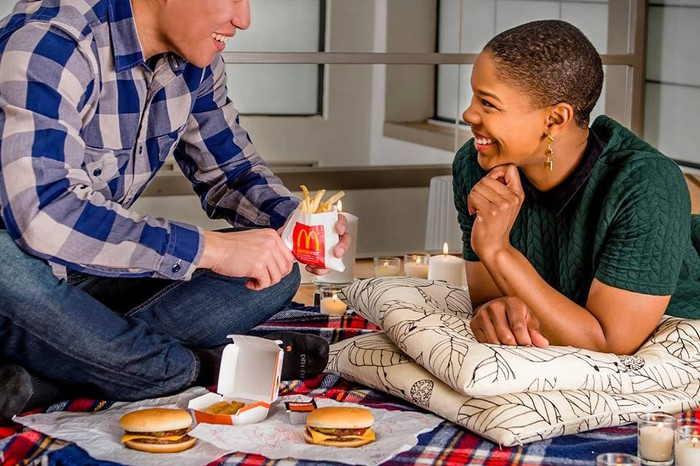 Couple sharing cheeseburgers and french fries