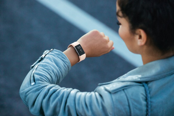 A woman looking at a Fitbit Charge 2 on her wrist.