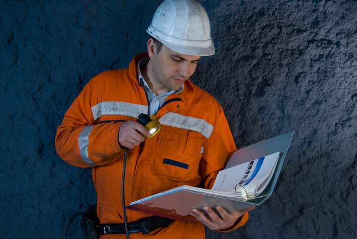 An engineer looking at a binder with a flashlight