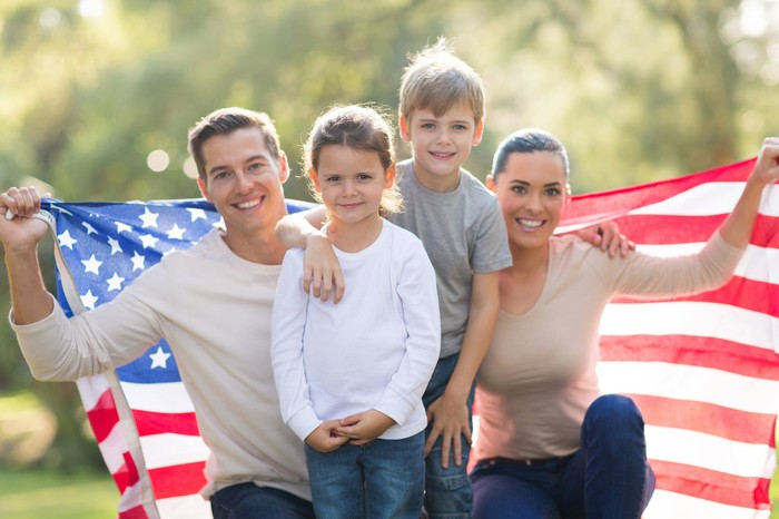 Smiling family holding up an American flag
