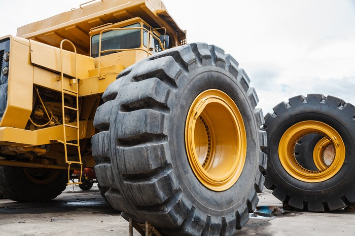 Large yellow construction truck with a closeup of a giant tire.
