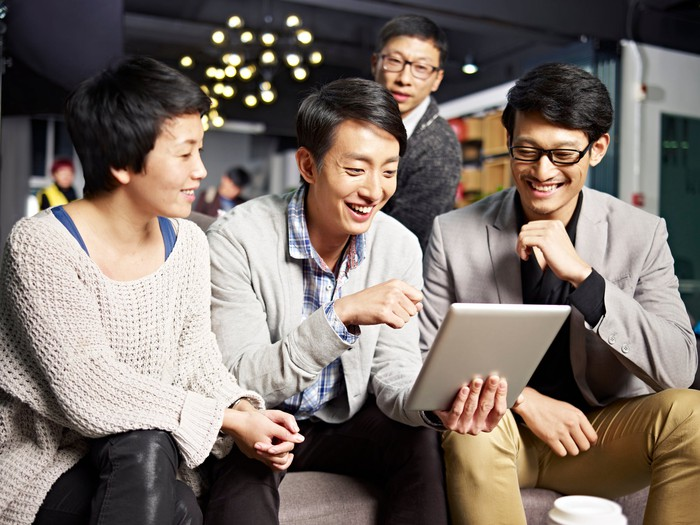 Four Asian people smiling while looking at a tablet.