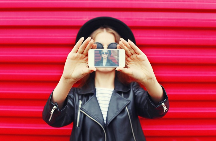 Fashionably dressed woman takes selfie with smartphone.