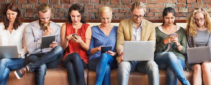 Men and women packed into a long couch, looking at laptops, tablets, and smartphones.