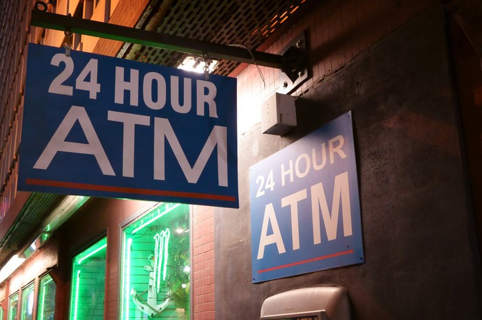 A sign for a 24-hour ATM.