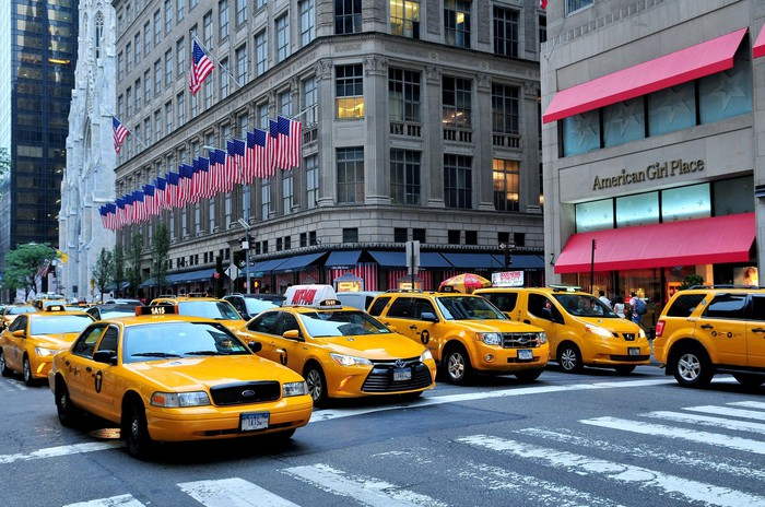 A horde of taxi cabs are driving down Manhattan's Fifth Avenue, past the Saks Fifth Avenue flagship store.