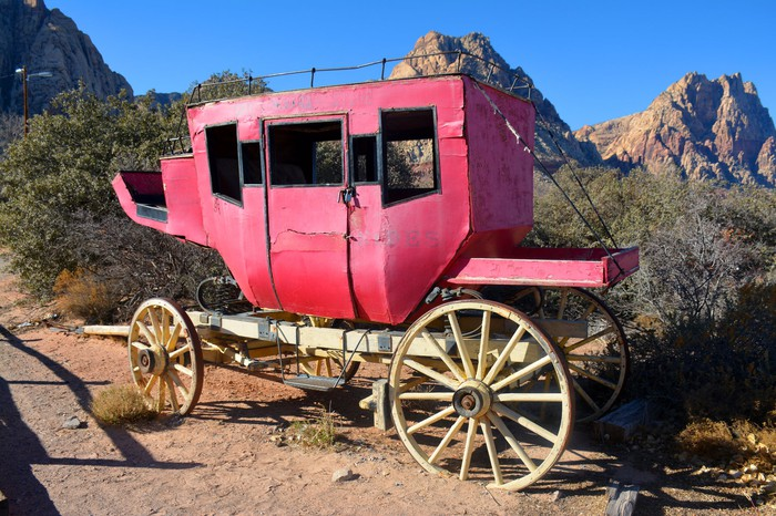 An old, red stagecoach parked in the desert.