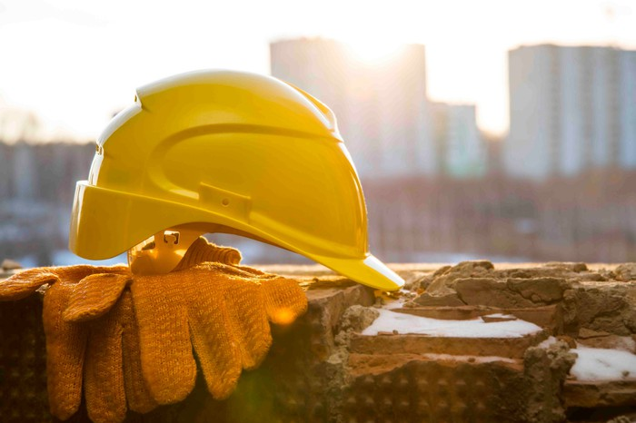 A yellow hard hat sitting on top of gloves on a ledge.