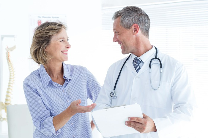 Middle-aged female patient smiling looking at face of smiling male physician who has a stethoscope around his neck and is holding papers.