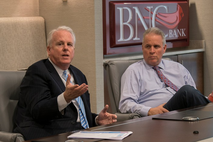 The CEOs of Pinnacle Financial Partners and BNC Bancorp sitting at a conference table.