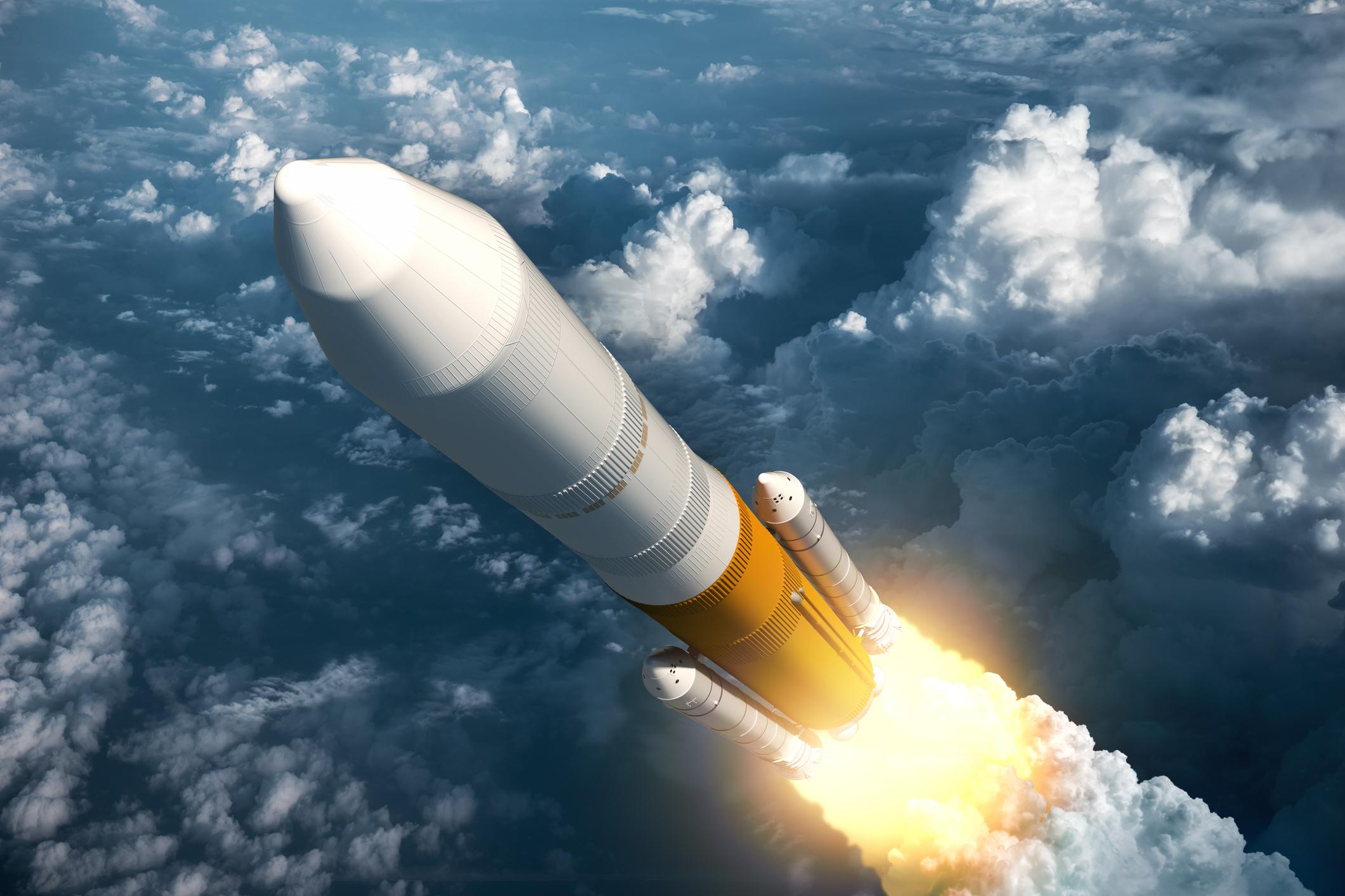 A rocket ascending above clouds